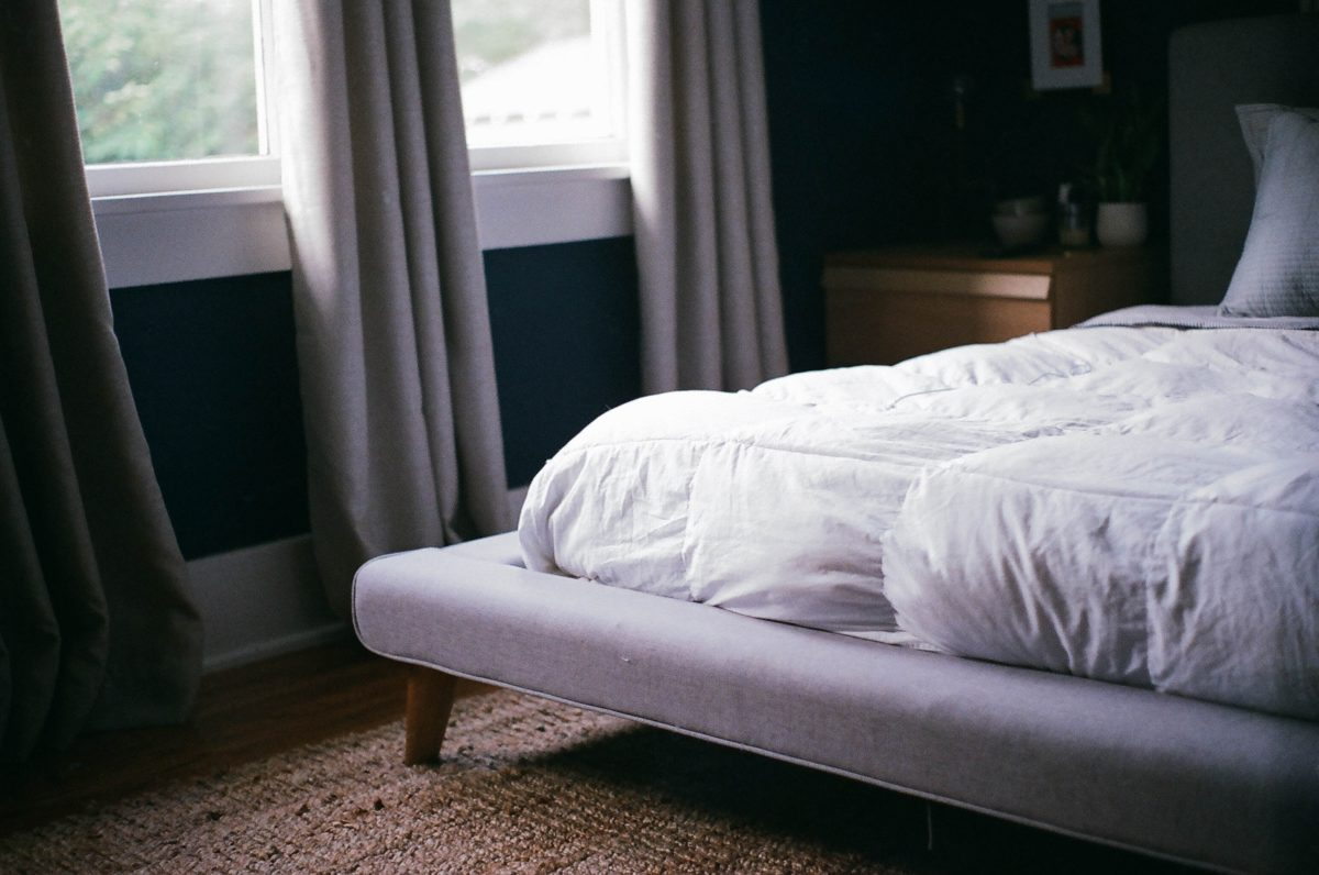 white bed by the window during daytime